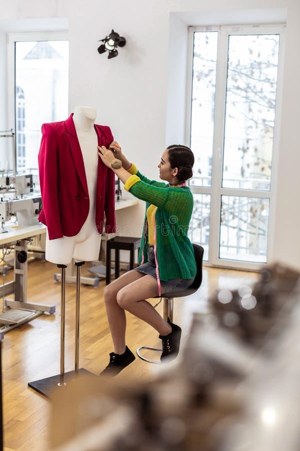 Costureira de cabelo escuro asiática bonita em uma saia curto que passa seu dia em uma sala de exposições imagem de stock royalty free