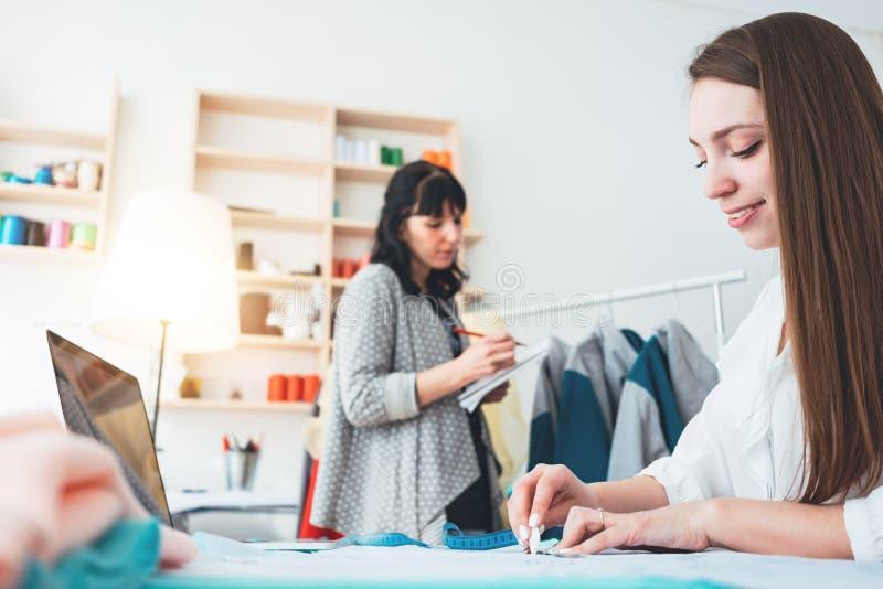 Costureira de duas mulheres que faz o roupa de grife na sala de exposições Costureira profissional fêmea nova que trabalha na cos imagens de stock royalty free
