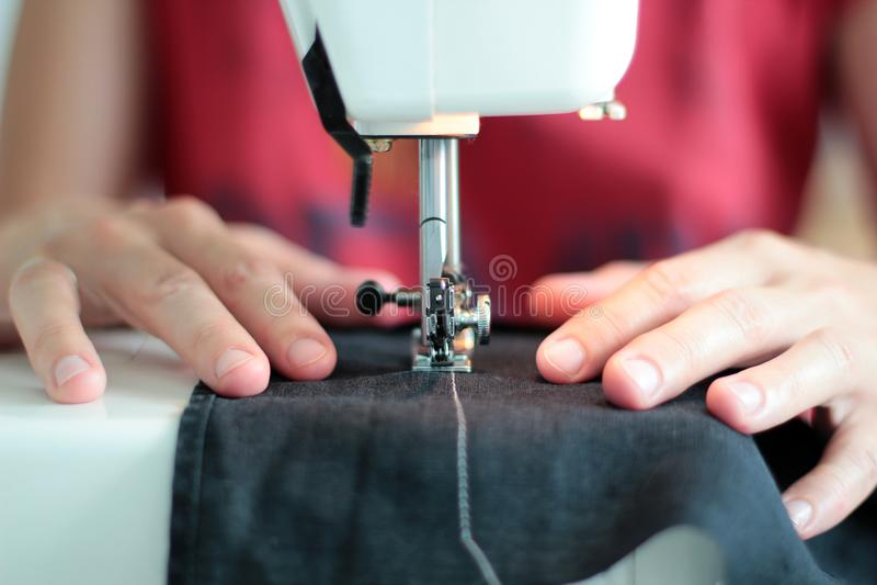 A costureira do close-up entrega o trabalho na máquina de costura em casa Processo da costura mãos da mulher atrás do close-up da fotografia de stock royalty free