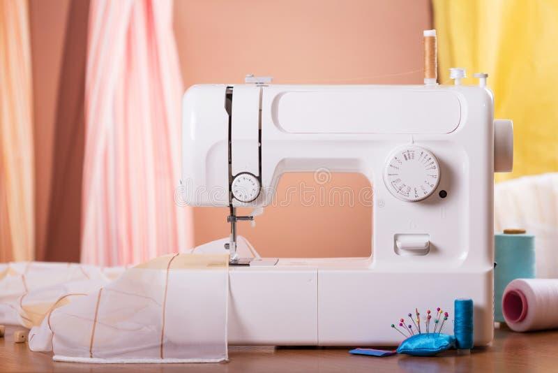 Costureira do local de trabalho Máquina de costura, telas e acessórios brancos fotos de stock