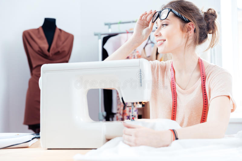 A costureira feliz da mulher costura na máquina de costura no estúdio fotografia de stock royalty free