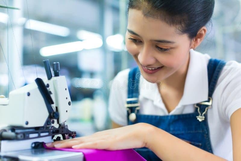 Costureira indonésia em uma fábrica de matéria têxtil fotografia de stock
