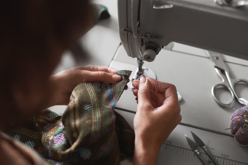 Costureira que trabalha na máquina de costura elétrica moderna que faz vestuários exclusivos no estúdio da forma foto de stock