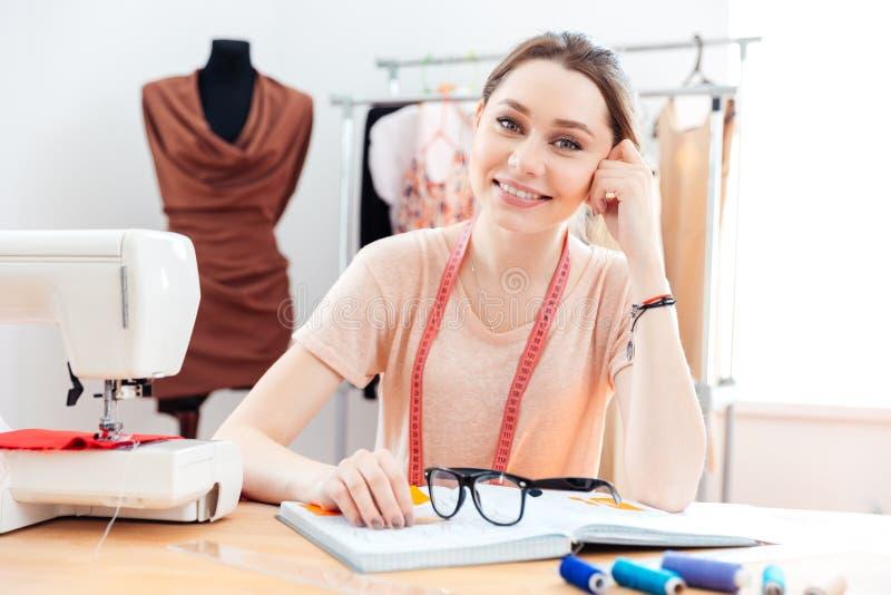 Costurera alegre de la mujer que trabaja en taller de costura imagenes de archivo
