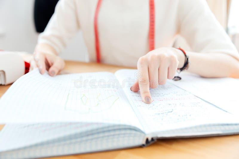 Costurera de la mujer joven que señala y que lee notas en cuaderno imagen de archivo libre de regalías