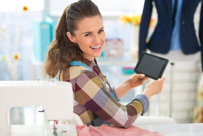 Costurera feliz que usa la PC de la tableta en el trabajo fotos de archivo