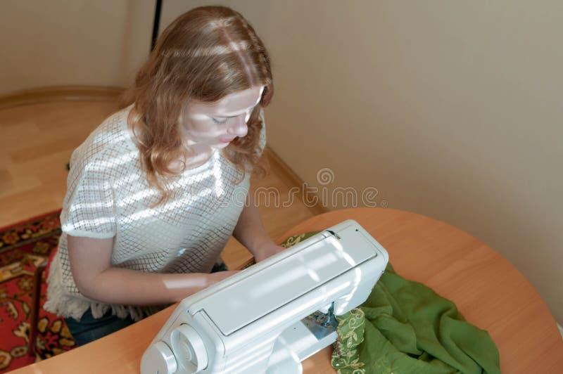 costurera que se sienta en la tabla con la máquina de coser, fotos de archivo libres de regalías