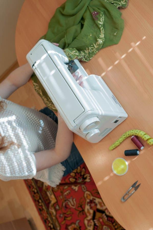 costurera que se sienta en la tabla de madera con la máquina de coser, trabajando cerca de ventana en estudio foto de archivo