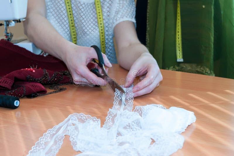 Costurera que se sienta en la tabla, máquina de coser y cortando el cordón con las tijeras en estudio de costura fotos de archivo