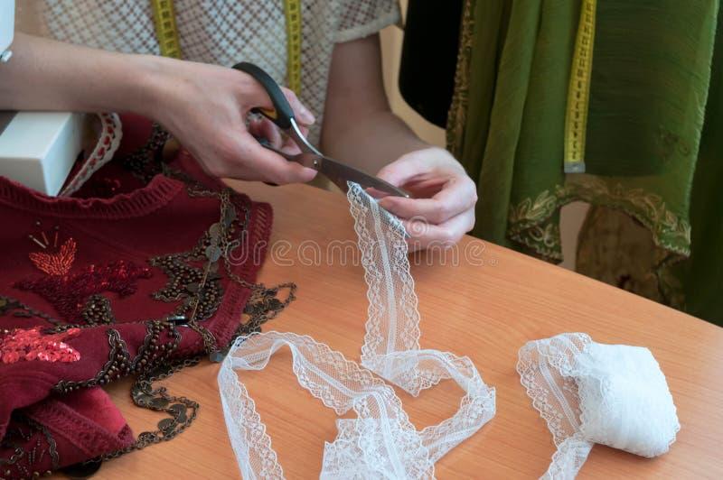 Costurera que se sienta en la tabla, máquina de coser y cortando el cordón con las tijeras en estudio de costura imagen de archivo