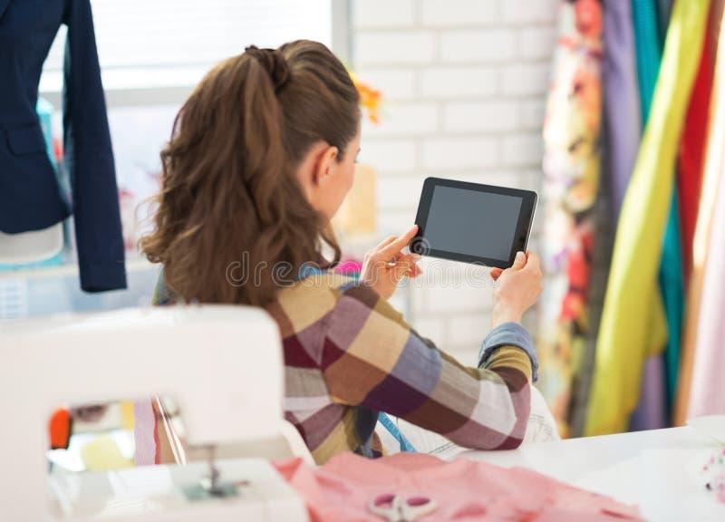 Costurera que usa la PC de la tableta en el trabajo Visión trasera imágenes de archivo libres de regalías