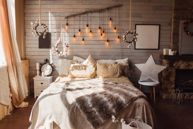 Cosy bedroom with eco decor. Wood and nature concept in interior of room. Scandinavian interior, real photo. Hygge decoration stock photo