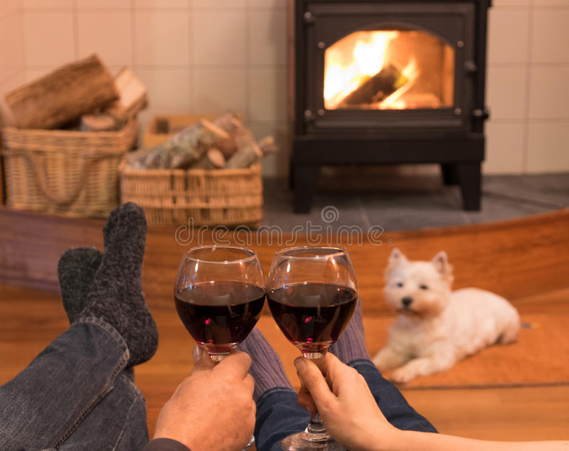 Cosy and companiable. Cosy couple by the fire with red wine and a west highland terrier westie dog stock photo