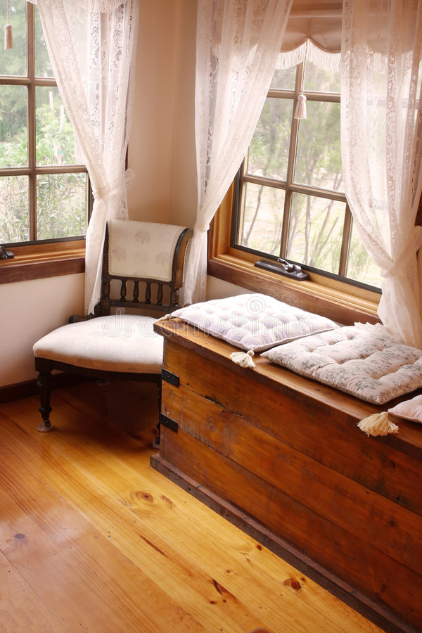 Cosy Corner. Of a Victorian country cottage, with cushioned window seat, and 19th century chair royalty free stock photography