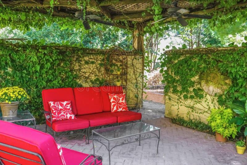 Cosy plenerowa żywa przestrzeń - Czerwony plenerowy meble na patiu pod obfitolistną altaną z podsufitowymi fan i winogradem z obrazy stock