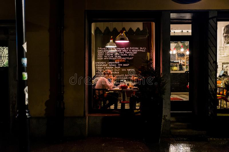 cosy Polish restaurant seen from outside, in a cold winters night in Krakow, Poland. The glass window has the menu written on it stock photo
