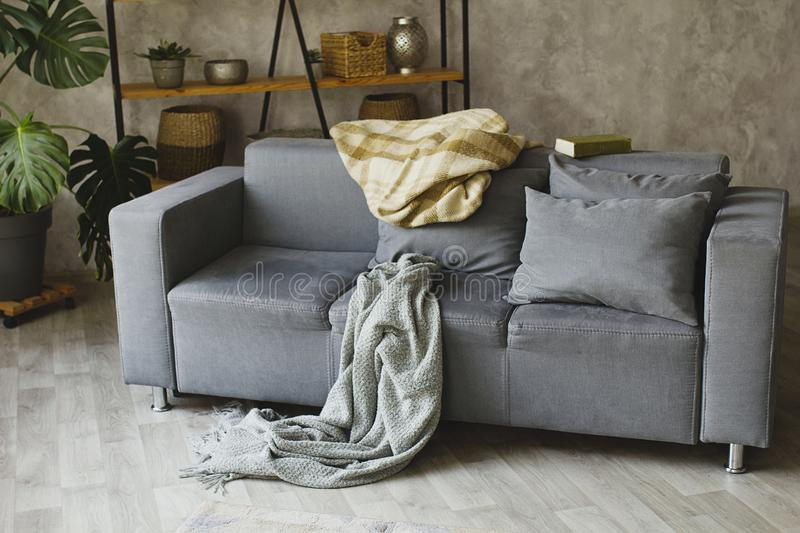 Cosy sofa with grey plaid and pillows. Hugge concept. stock image