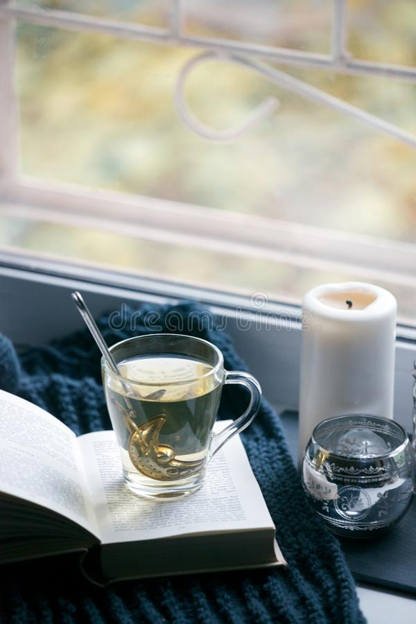 Cosy and soft winter, autumn, fall background, knitted decor and books on an windowsill. Christmas holidays at home, calmness. Closeup, weekend concept stock images