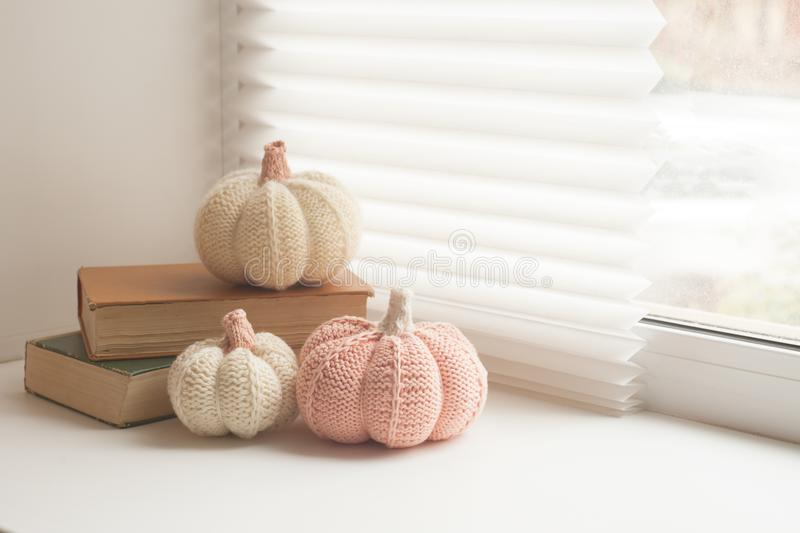 Cosy and soft winter, autumn, fall background, knitted decor and books on an windowsill. Christmas, thanksgiving holidays at home. Calmness closeup, weekend stock photo