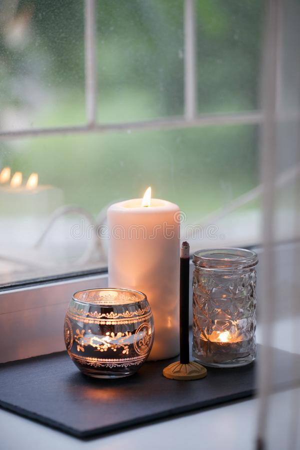 Cosy and soft winter autumn home background, karoma stick and candles on an stone board on windowsill. Christmas or seasonal royalty free stock image
