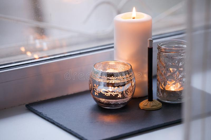 Cosy and soft winter autumn home background, karoma stick and candles on an stone board on windowsill. Christmas or seasonal. Holidays at home. Interior stock photos