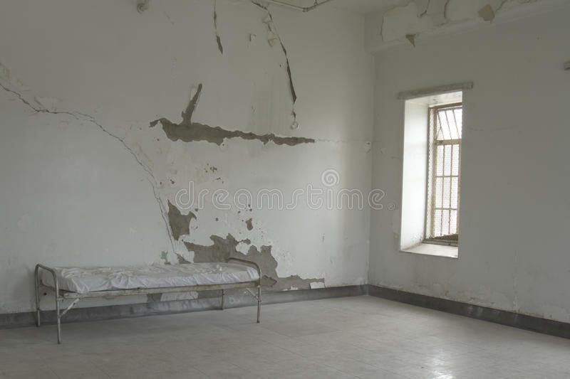 Cot in empty room. Of old mental illness asylum royalty free stock image