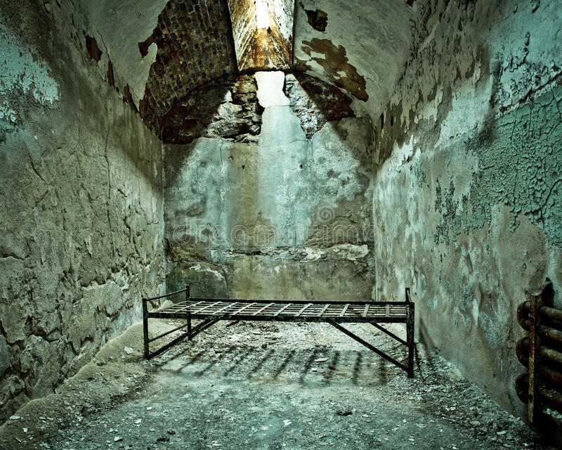 Cot in Prison Cell. Cot in empty crumbling prison cell at Eastern State Penitentiary stock image