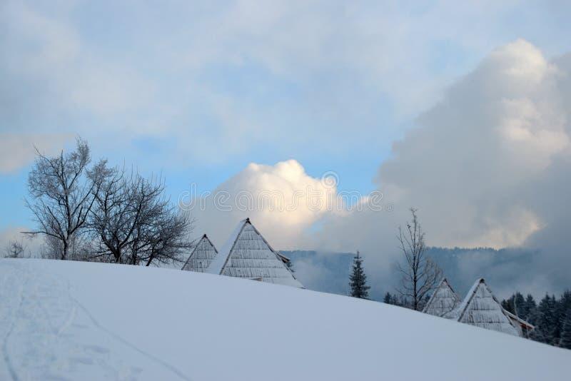 Cotage под снегом, горами и небом в задней части стоковые фотографии rf