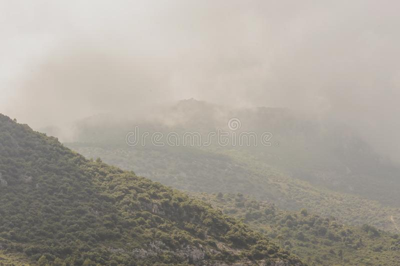 Mountains in the clouds behind the medieval Provencal village of Roquebrune Cap Martin. Cote d`Azur French Riviera is situated in the southern eastern part of royalty free stock image