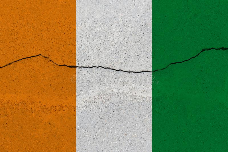 Cote d `ivoire - Ivory Coast flag on concrete wall with crack. Patriotic grunge background. National flag of Cote d `ivoire - Ivory Coast stock images