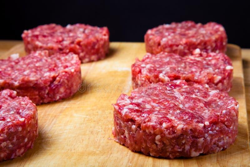 Cotoletta cruda di carne tritata su un tagliere di legno Reparto basso fotografia stock
