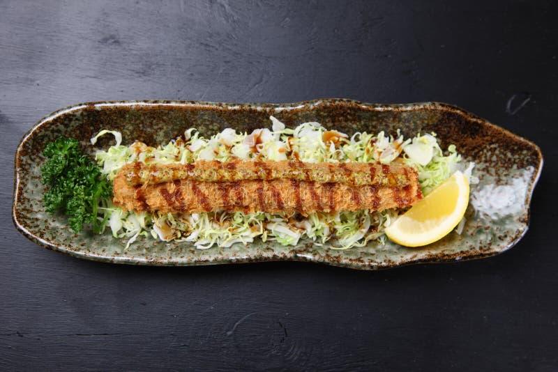 Cotoletta del raccordo della carne di maiale del bastone su un tavolo da pranzo fotografia stock