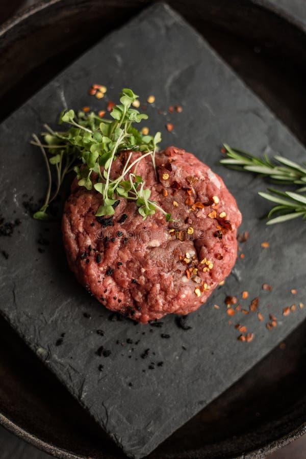 Cotolette crude della bistecca della carne della carne tritata con le erbe e le spezie sul bordo nero Ristorante fotografie stock libere da diritti