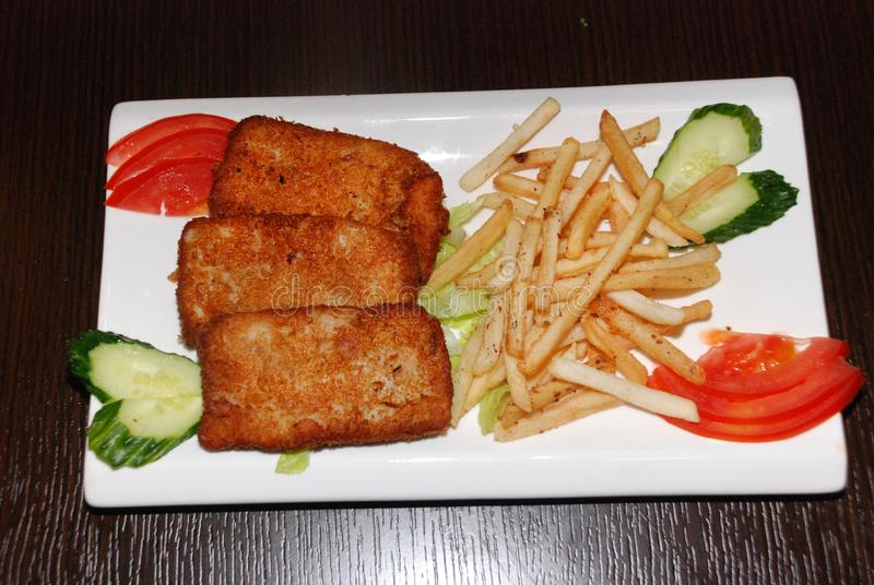 Cotolette fritte del pesce con le patate fritte e le verdure sul piatto bianco fotografie stock