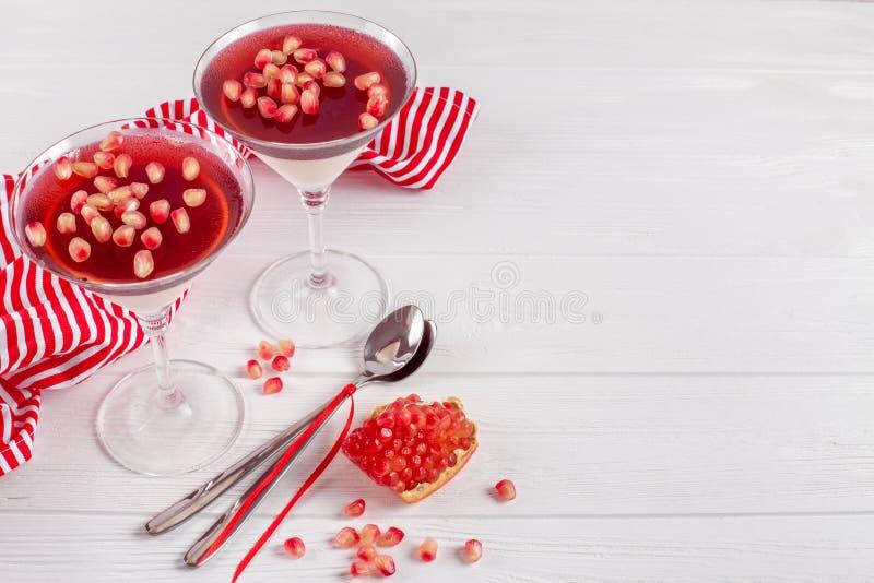 Cotta crémeux de panna de vanille avec la gelée rouge en beaux verres, grenade mûre fraîche sur le fond en bois blanc photos libres de droits