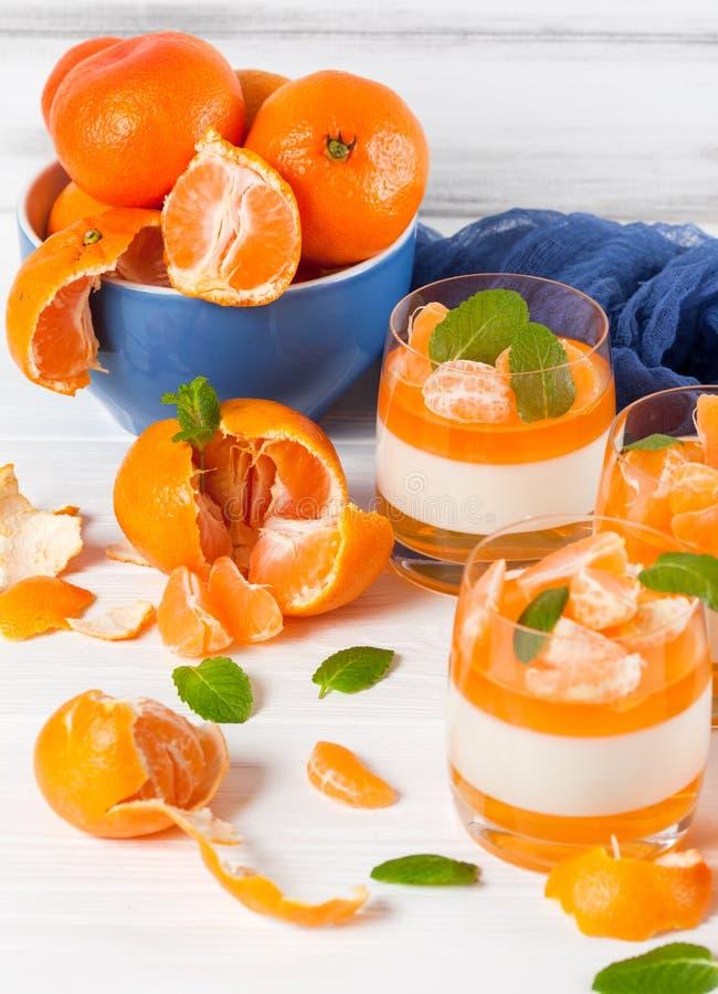 Cotta cremoso do panna com geleia alaranjada em vidros bonitos, o mandarino maduro fresco, matéria têxtil azul no fundo de madeir imagem de stock royalty free