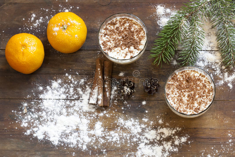 Cotta panna βανίλιας με τη σοκολάτα, tangerines, τους κώνους, την κανέλα και τα καρύδια στο ντεκόρ Χριστουγέννων με το χριστουγεν στοκ εικόνα