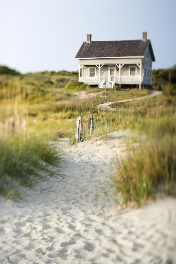 Cottage on Beach. A sandy trail surrounded by brush leading up to a cottage on the beach. Vertical shot royalty free stock photo