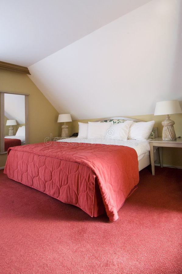 Cottage Bed. A luxury double bed in a warm cottage bed room stock photography