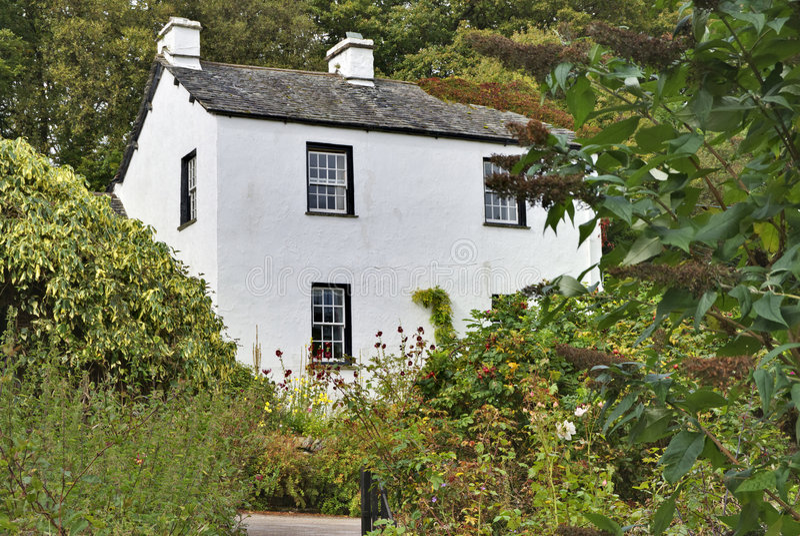 Cottage bianco inglese in terreno boscoso immagine stock libera da diritti
