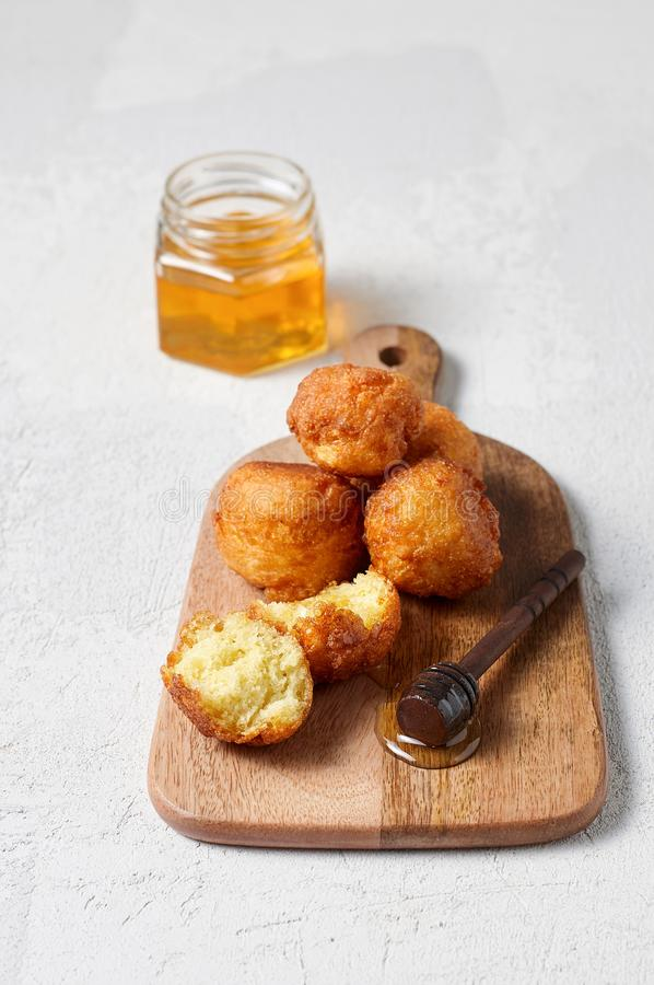 Cottage cheese balls doughnuts is jam-packed with jelly filling on wooden cut board and glass jar honey stock image