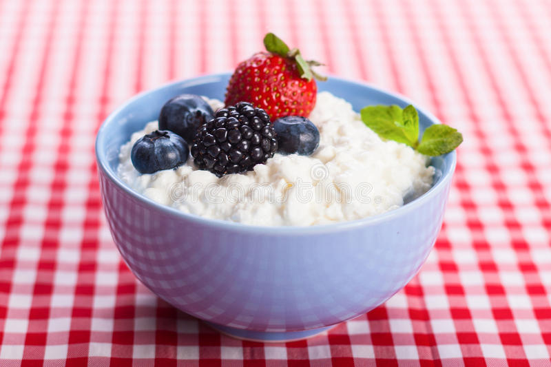 Cottage cheese with berries. Close-up of homemade cottage cheese with strawberry, blueberries and blackberry, horizontal stock photo royalty free illustration
