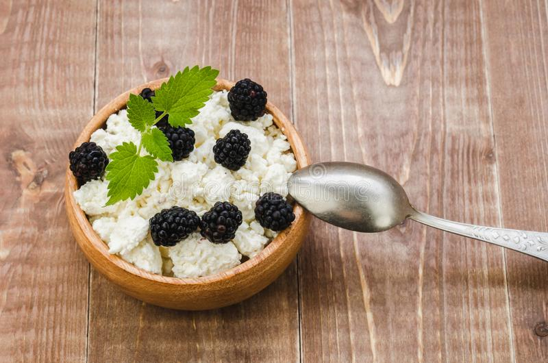 Cottage cheese with blackberry in a wooden plate/cottage cheese with blackberry in a wooden plate. Top view. Curd, blackberries, bowl, background, food stock photo