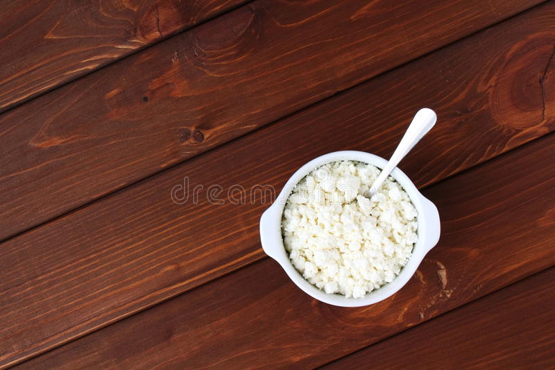 Cottage cheese. Bowl of cottage cheese on wooden background royalty free stock photography