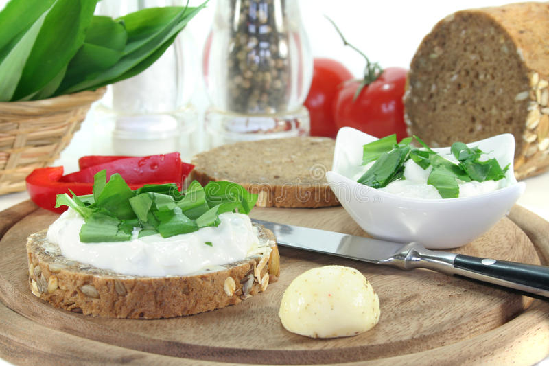 Cottage cheese bread with wild garlic. A slice of bread with cottage cheese and freshly chopped wild garlic royalty free stock photography