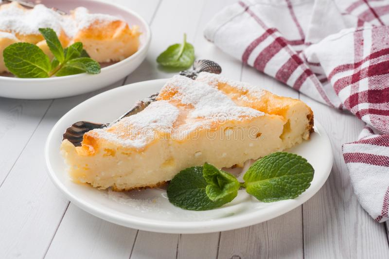 Cottage cheese casserole on a plate with powdered sugar and mint leaves. Selective focus stock images
