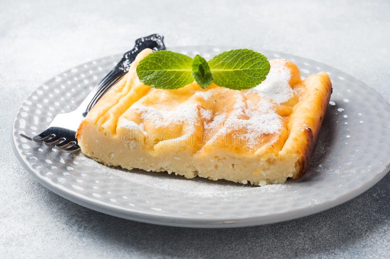 Cottage cheese casserole on a plate with powdered sugar and mint leaves. Selective focus stock photography