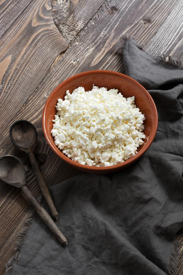 Cottage cheese in a ceramic bowl, wooden spoons, napkin on a wooden brown table. royalty free stock photos