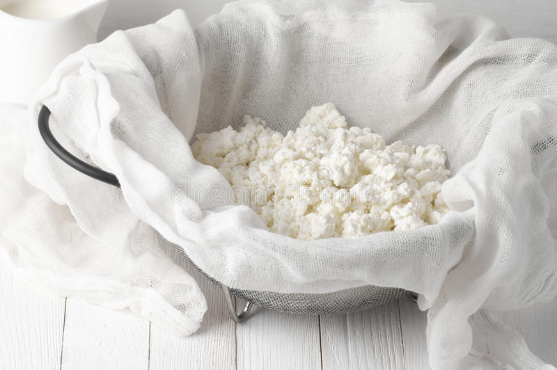 Cottage cheese in cheesecloth stock image