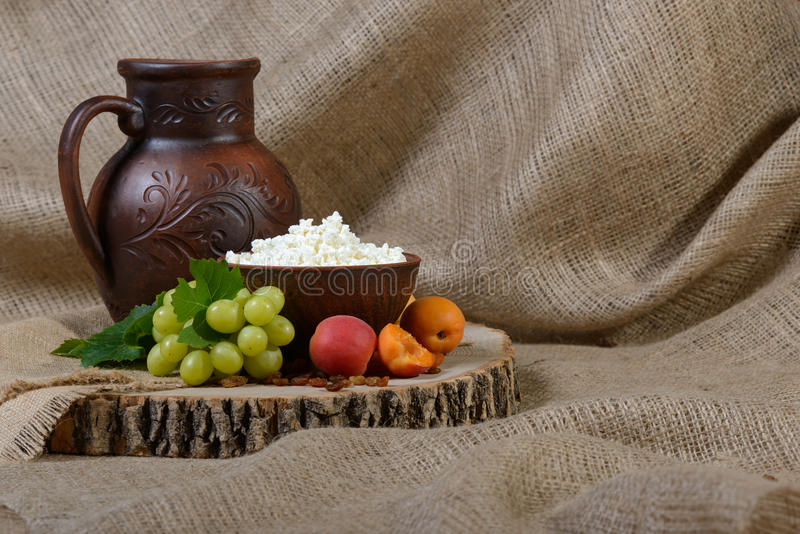 Cottage cheese in a clay dish, milk, grape, apricots on wooden background. stock image